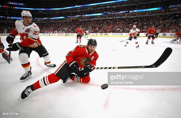 Duncan Keith of the Chicago Blackhawks tries to control the puck in front of Sean Monahan of the Calgary Flames at the United Center on February 6...