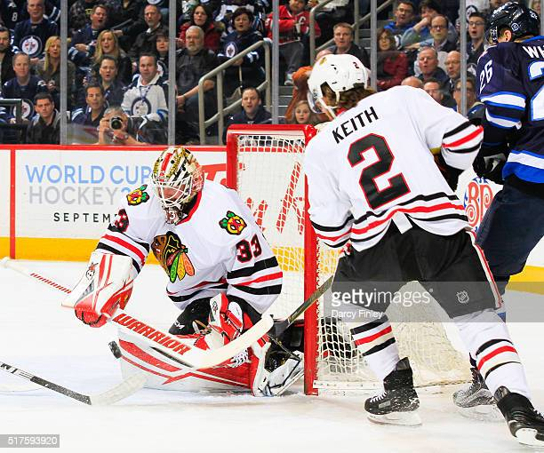 Duncan Keith of the Chicago Blackhawks watches as goaltender Scott Darling makes a stick save during first period action against the Winnipeg Jets at...