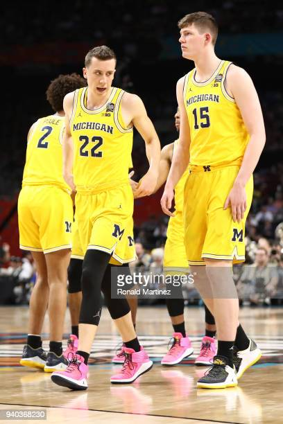 Duncan Robinson and Jon Teske of the Michigan Wolverines discuss the play against the Loyola Ramblers in the second half during the 2018 NCAA Men's...