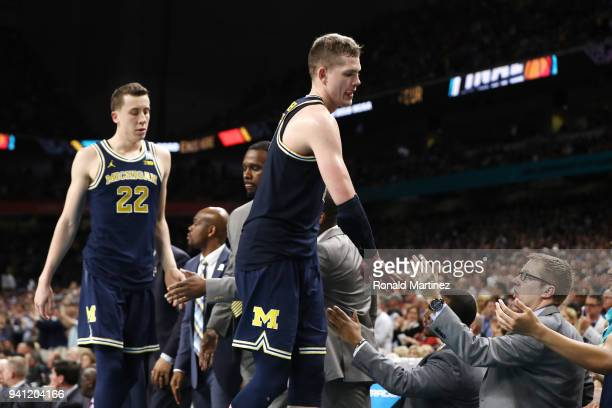 Duncan Robinson and Moritz Wagner of the Michigan Wolverines come off the court late in the second half against the Villanova Wildcats during the...