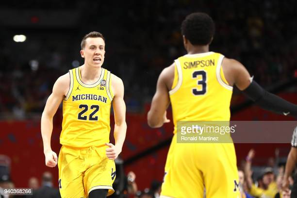 Duncan Robinson and Zavier Simpson of the Michigan Wolverines celebrate the play against the Loyola Ramblers in the second half during the 2018 NCAA...