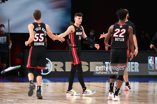 Duncan Robinson high-fives Tyler Herro of the Miami Heat during Game Three of the NBA Finals on October 4, 2020 at AdventHealth Arena in Orlando,...