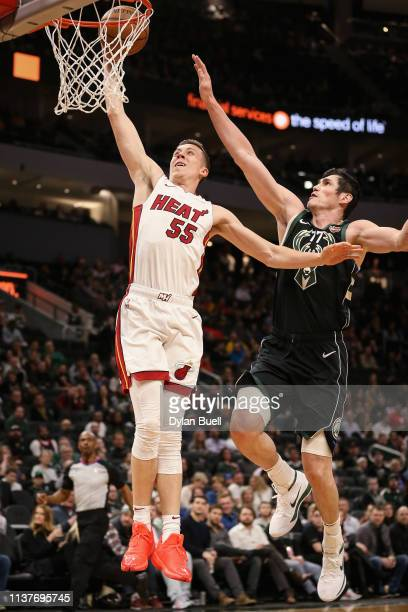 Duncan Robinson of the Miami Heat dunks the ball past Ersan Ilyasova of the Milwaukee Bucks in the fourth quarter at the Fiserv Forum on March 22...