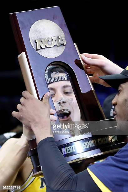 Duncan Robinson of the Michigan Wolverines celebrates with the West Regional trophy after their 5854 victory against the Florida State Seminoles in...