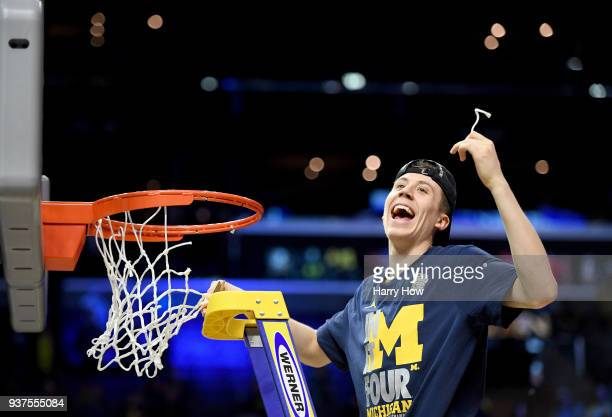 Duncan Robinson of the Michigan Wolverines cuts down the net after the Wolverines 5854 victory against the Florida State Seminoles in the 2018 NCAA...