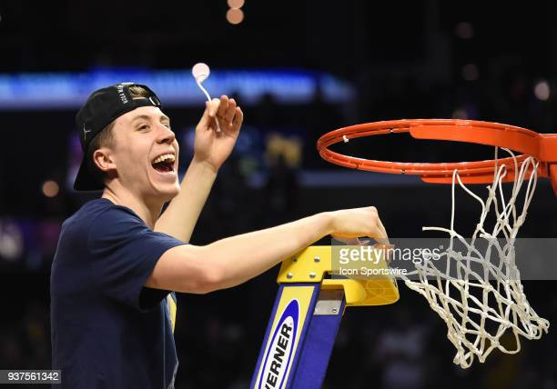 Duncan Robinson of the Michigan Wolverines cuts down the net to celebrate the victory during the NCAA Division I Men's Championship Elite Eight round...
