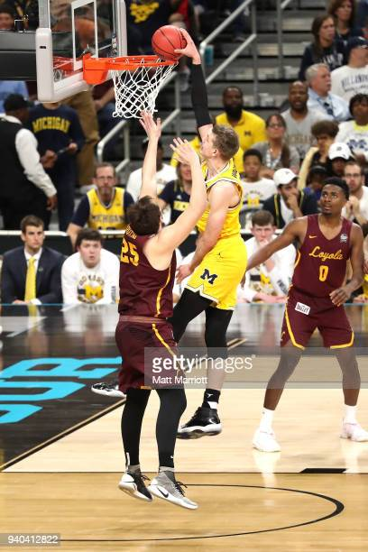 Duncan Robinson of the Michigan Wolverines dunks against Cameron Krutwig of the Loyola Ramblers during the first half in the 2018 NCAA Men's Final...