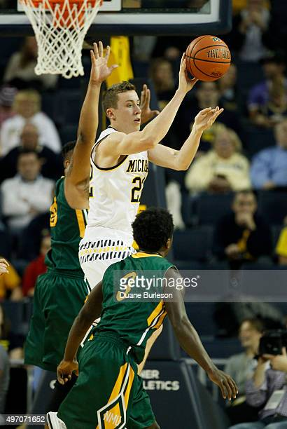 Duncan Robinson of the Michigan Wolverines passes the ball against Terry Nash of the Northern Michigan Wildcats during the second half at Crisler...