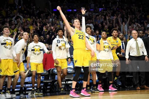 Duncan Robinson of the Michigan Wolverines reacts in front of the bench as he makes a threepointer in the second half while taking on the Florida...