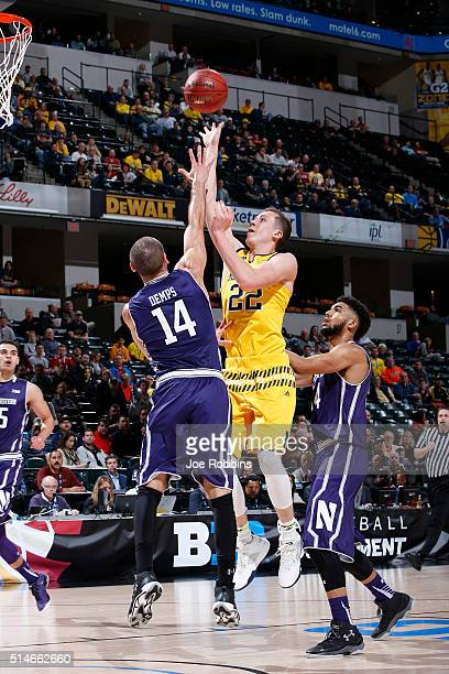 Duncan Robinson of the Michigan Wolverines shoots against Tre Demps of the Northwestern Wildcats in the second round of the Big Ten Basketball...