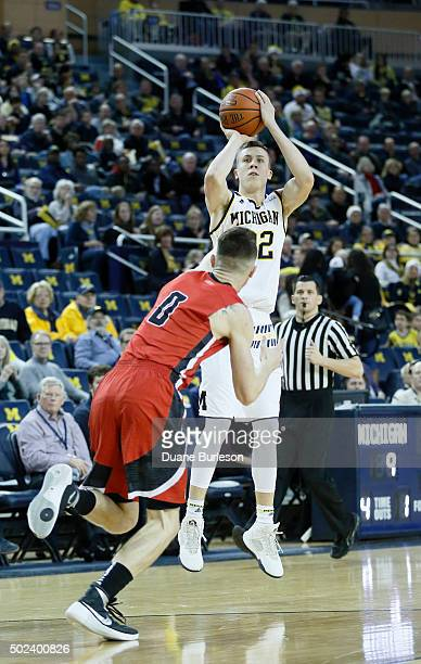Duncan Robinson of the Michigan Wolverines takes a shot against Matt Donlan of the Youngstown State Penguins during the first half at Crisler Arena...