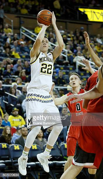 Duncan Robinson of the Michigan Wolverines takes a shot as Matt Donlan of the Youngstown State Penguins looks on during the first half at Crisler...