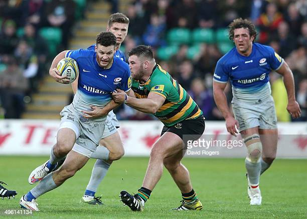 Duncan Taylor of Saracens is held by Kieran Brookes during the Aviva Premiership match between Northampton Saints and Saracens at Franklin's Gardens...