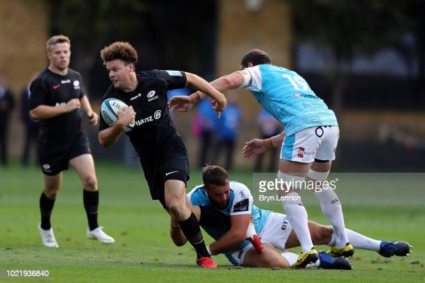 Duncan Taylor of Saracens is tackled by Alex Jeffries and Giorgi Nemsadze of Ospreys during the preseason match between Saracens and Ospreys at the...