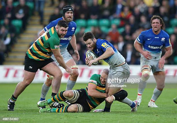 Duncan Taylor of Saracens is tackled by Sam Dickinson and Kieran Brookes during the Aviva Premiership match between Northampton Saints and Saracens...