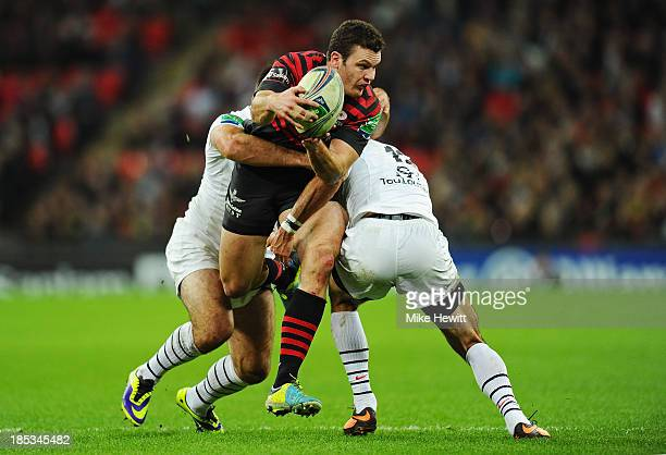 Duncan Taylor of Saracens looks to offload as he is tackled by Clement Poitrenaud of Toulouse during the Heineken Cup pool three match between...
