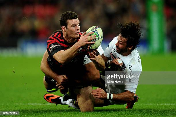 Duncan Taylor of Saracens offloads as he is tackled by Clement Poitrenaud of Toulouse during the Heineken Cup pool three match between Saracens and...
