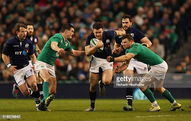 Duncan Taylor of Scotland is tackled by Jonathan Sexton and Robbie Henshaw of Ireland during the RBS Six Nations match between Ireland and Scotland...