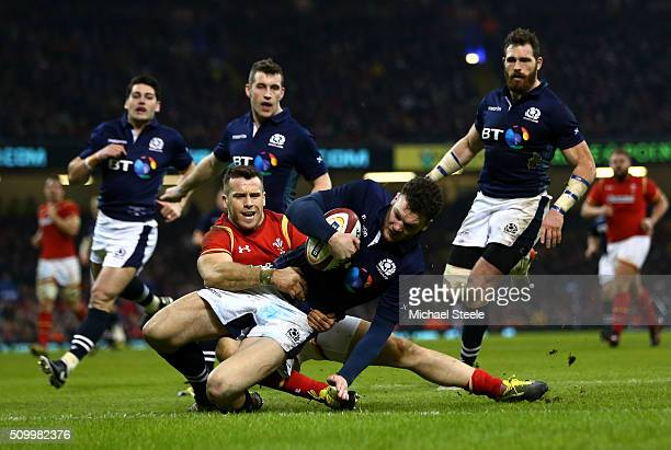 Duncan Taylor of Scotland scores his team's second try despite the tackle from Gareth Davies of Wales during the RBS Six Nations match between Wales...