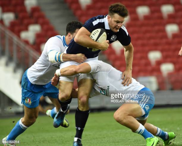 Duncan Taylor of Scotland tackled by two Italian players during their rugby Test match between Italy against Scotland at the National Stadium on June...