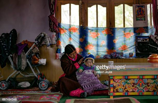 Dundup Angmo holds her friends child at her home in Yarat village which is dependent on solar energy on June 14 2017 in Ladakh India She says that...