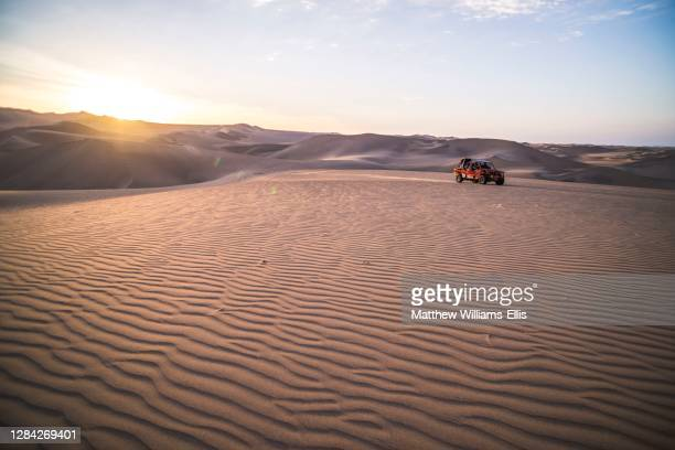 Dune buggying in sand dunes at sunset in the desert at Huacachina, Ica Region, Peru, South America.