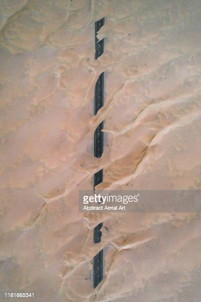dunes crossing a straight road in the desert, dubai, united arab emirates - the hobbit: an unexpected journey stock pictures, royalty-free photos & images