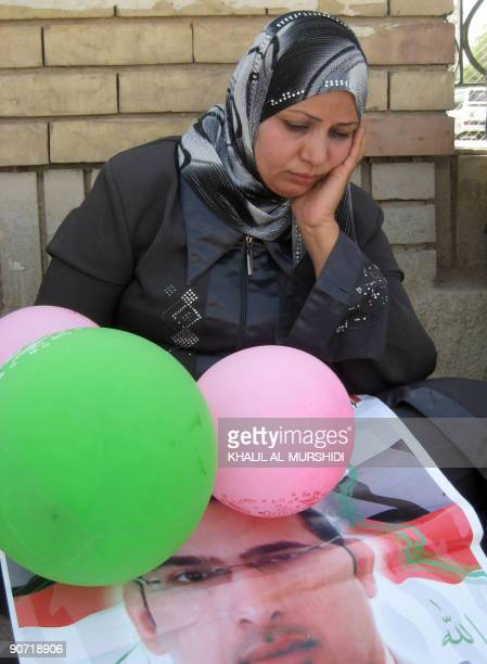 Dunia the sister of jailed Iraqi television journalist Muntazer alZaidi sits on the ground following an announcement that her brother's imminent...