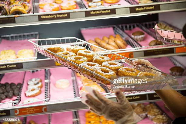 Dunkin' Donuts employee places a fresh tray of croissant doughnuts on the shelf on November 3 2014 in New York City The pastry which began selling at...