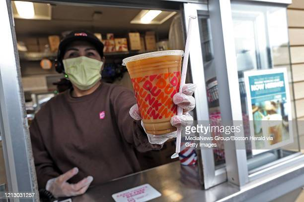 Dunkin' worker hands a coffee out of a drive-thru window wearing gloves and a mask as the Coronavirus continues to spread on March 17, 2020 in...