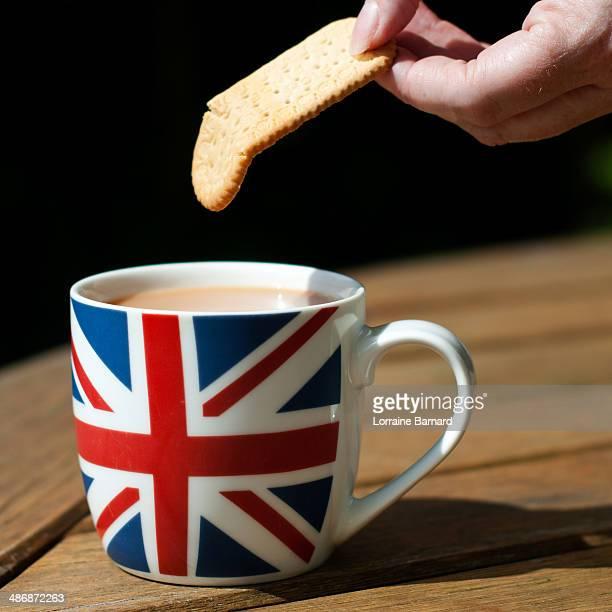 dunking bisciut into mug of tea - britische kultur stock-fotos und bilder