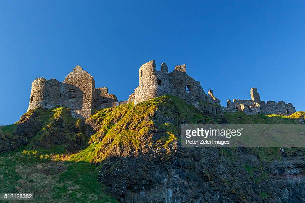 dunluce castle, a now-ruined medieval castle in northern ireland - dunluce castle stock photos and pictures