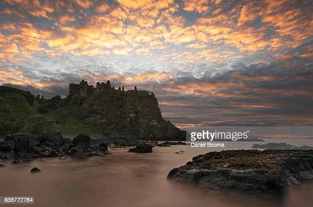 dunluce castle during colorful sunset - dunluce castle stock photos and pictures