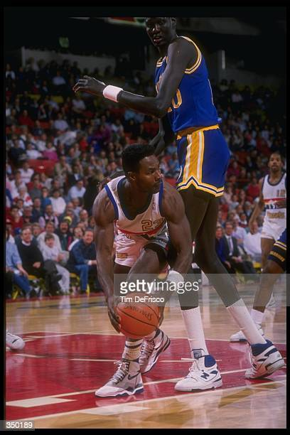 T R Dunn of the Denver Nuggets looks to pass around center Manute Bol of the Golden State Warriors during a Nuggets game versus the Warriors at the...