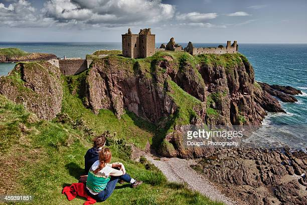 dunnottar castle and young couple - dunnottar castle stock pictures, royalty-free photos & images