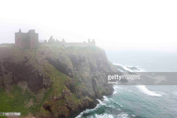 Dunnottar Castle in the mist, ruined medieval fortress near Stonehaven on sea cliff along the North Sea coast, Aberdeenshire, Scotland, UK.