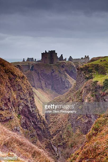 dunnottar castle under storm clouds. - dunnottar castle stock pictures, royalty-free photos & images
