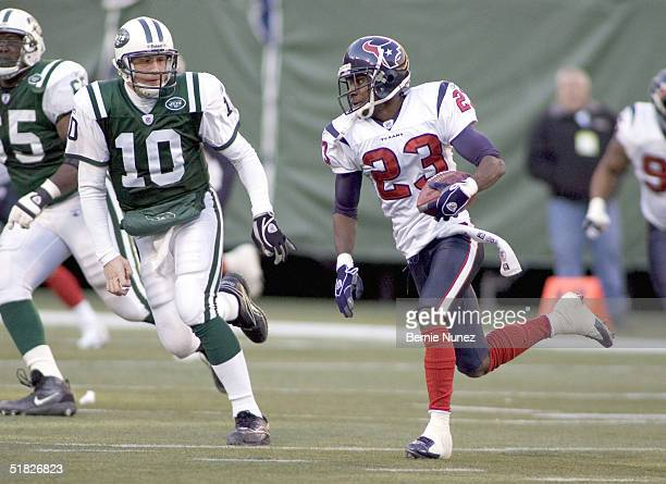 Dunta Robinson of the Houston Texans runs with an interception as Chad Pennington of the New York Jets pursues on December 5 2004 at Giants Stadium...