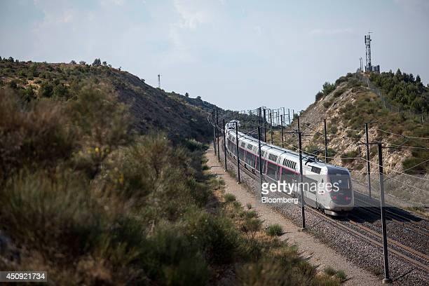 A TGV duplex highspeed train operated by Societe Nationale des Chemins de Fer and manufactured by Alstom SA heads through the hills outside the city...