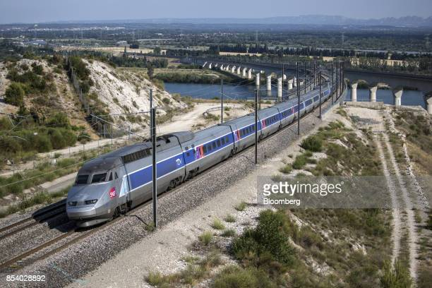 TGV duplex highspeed train operated by Societe Nationale des Chemins de Fer and manufactured by Alstom SA crosses the River Rhone outside Avignon as...
