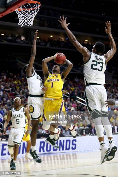 Dupree McBrayer of the Minnesota Golden Gophers shoots the ball against Aaron Henry of the Michigan State Spartans during the second half in the...