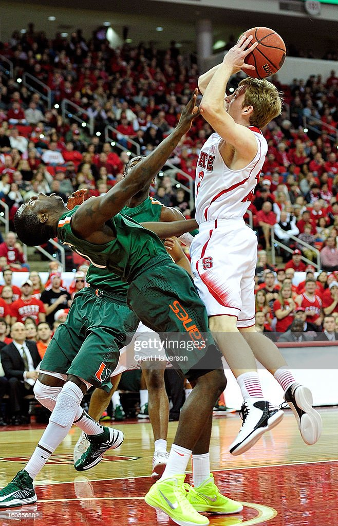 Durand Scott #1 of the Miami Hurricanes is called for a blocking foul as he collides with Tyler Lewis #12 of the North Carolina State Wolfpack during play at PNC Arena on February 2, 2013 in Raleigh, North Carolina.