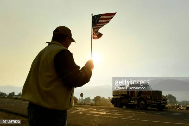 Durango resident Ted Hood stands along Highway 550 and waves to firefighters as they head back out to the 416 Fire on June 14 2018 in Hermosa...
