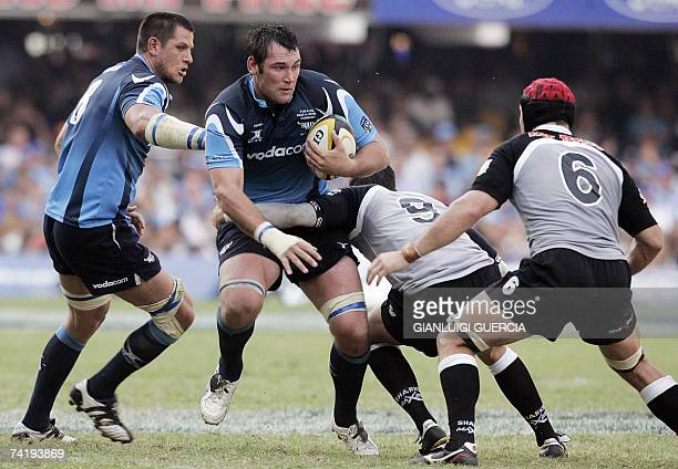 Bulls flank Pedrie Wannenburg helped by Bulls lock Pierre Spies as he tries to break trough the defense of, Sharks Jaques Botes and Sharks Ruan...