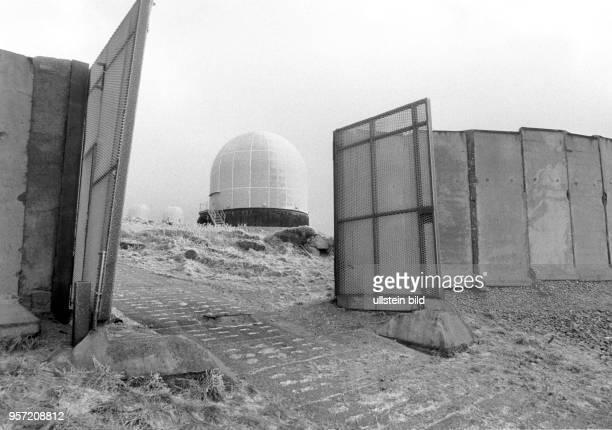 Durch ein geöffnetes Metalltor in der Grenzmauer am Brocken sind Radarkuppeln sogenannte Radome auf dem Brocken zu sehen aufgenommen im Januar 1990...