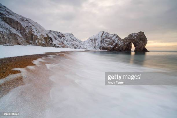 durdle door in the snow - coastline stock photos and pictures