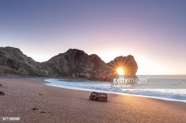 durdle door natural arch formation at sunrise, dorset, england, uk - naturwunder stock-fotos und bilder