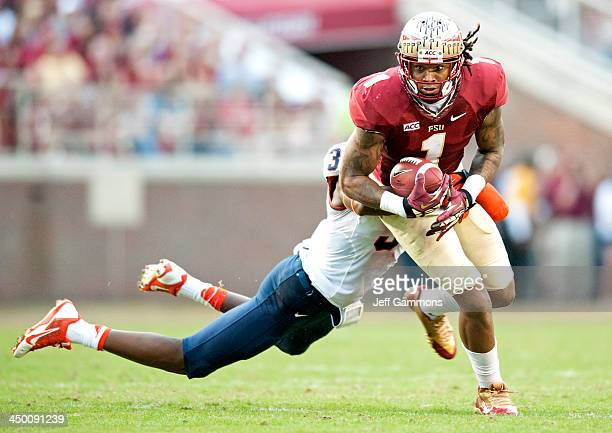 Durell Eskridge of the Syracuse Orange attempts to take down Kelvin Benjamin of theFlorida State Seminoles during the first half at Doak Campbell...