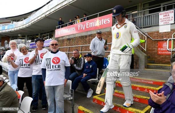 Durham batsman Keaton Jennings walks out to bat as Durham supporters with 'It's not cricket' TShirts look on before day one of the Specsavers County...