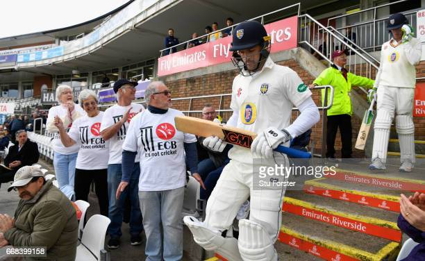 Durham opening batsmen Stephen Cook and Keaton Jennings walk out to bat as Durham supporters with 'It's not cricket' TShirts look on before day one...